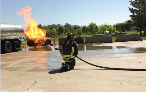A PFA firefighter takes part in a live burn during PFA's 2017 High School Fire Camp.